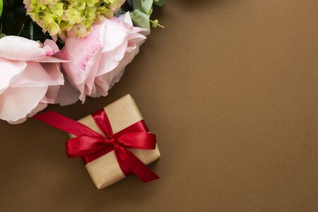Gift box top view, red bow and pink roses, brown background.