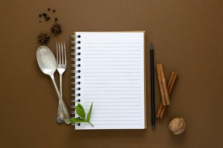 Open notebook and food condiments, fork and spoon.