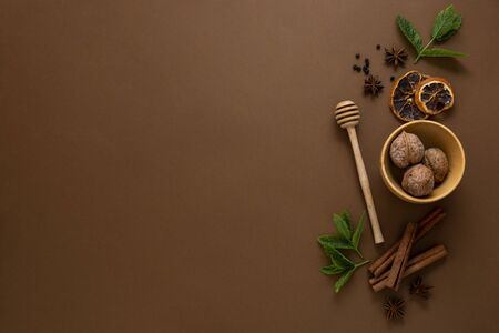 Condiments and spices, honey spoon, anise star, cinnamon sticks, mint leaves, brown background top view Stock Photo
