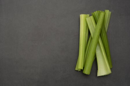 Fresh celery sticks on gray