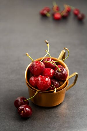 Fresh summer fruits, cherries in metal cups, gray background. Stock Photo