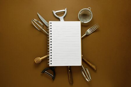 Cooking concept. Kitchen tools and empty note book. Brown background. Stock Photo