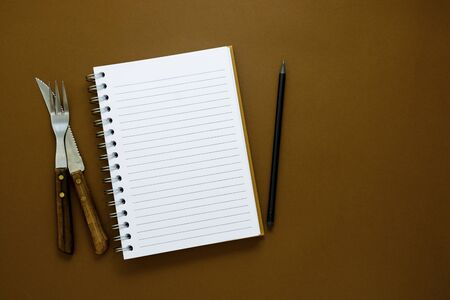 Empty note book for notes, text or recipes. Brown background with copy space.