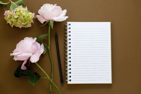 Open note book with flowers - roses, hydrangea. Brown background. Flat lay. Stock Photo