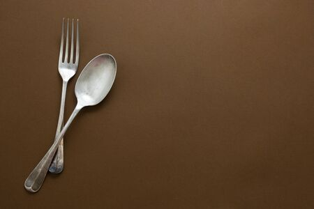 Spoon and fork, vintage cutlery isolated brown background, copy space for text. Food, recipe menu mockup.