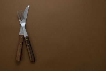 Recipe, food cooking mockup. Vintage fork and knife with wooden handle. Copy space for text. Stock Photo
