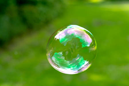 Soap Bubble isolated on green summer background. Kids fun activity.
