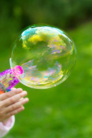 Making soap bubble outdoor. Summer fun activity for kids. Abstract education, play games concept. Stock Photo