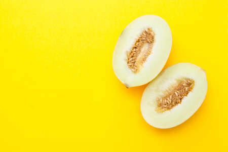 Cut ripe melon isolated on yellow background. Copy space for text.