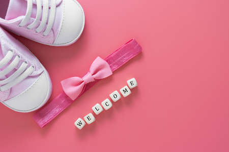 Baby girl pink background with newborn shoes, bow and Welcome words. Baby flat lay. Stock Photo