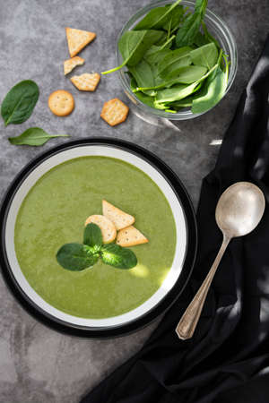 Green creamy vegetable soup with crackers. Healthy spinach, broccoli vegetarian detox food. Stock Photo