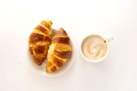 Croissant and a cup of coffee. Breakfast concept. White background.