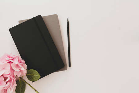 Table top with notebook with pencil and pink hydrangea flower. Copy space.