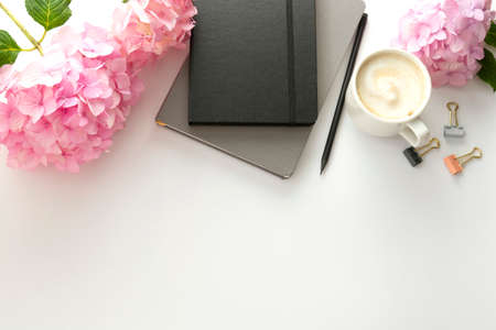 Table top of work space, feminine background. Cup of coffee with pink hydrangea and notebooks.