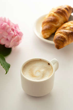 Croissant and a cup of coffee with pink hydrangea on background. Breakfast concept. 免版税图像