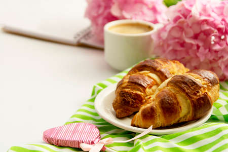 Breakfast with croissants, pink rose flower, petals, vintage plates and black coffee composition. Flat lay, top view