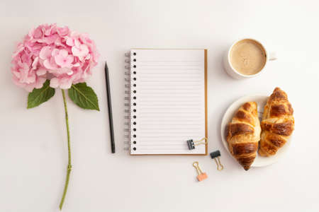 Table top, work space with notebook, cup of coffee and croissant, pink hydrangea. White background. Stock Photo