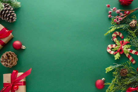 Christmas green background with winter decorations, gift boxes, fir branches, pine cones and red baubles. Copy space, flat lay. 免版税图像