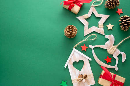 Christmas green background with winter rustic wooden decorations, gift boxes. Copy space, flat lay.