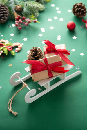 Sleigh with Christmas presents and winter decorations, green background.