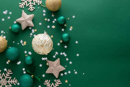 Christmas background with winter decorations, stars, baubles over green background. 免版税图像