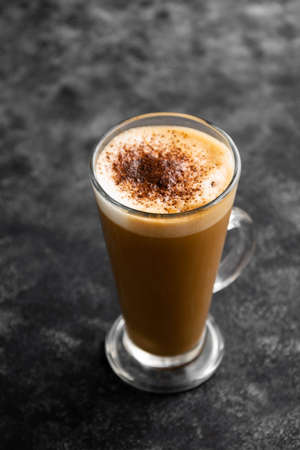 Hot chocolate drink. Tall glass up of fresh coffee latte with whipped cream, isolated on dark background