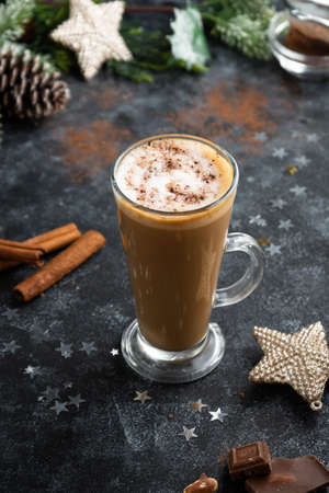Christmas or winter hot chocolate drink. Tall glass up of fresh coffee latte with whipped cream, isolated on dark background 免版税图像