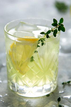 Refreshing yellow lemon glass of summer drink in glass. Soda lemonade drink with herb. 免版税图像