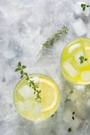 Refreshing yellow lemon glass of summer drink in glass. Soda lemonade drink, top view. 免版税图像