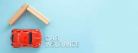 Corby, United Kingdom - 02. 02. 2021. Car insurance words banner red car model and wooden roof over blue background, copy space 免版税图像