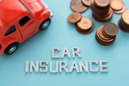 Corby, United Kingdom - 02. 02. 2021. Car insurance words, red car model and coins over blue background, copy space 免版税图像