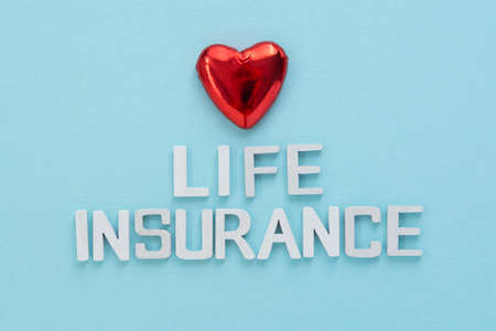 Life insurance text. Red heart over blue background.