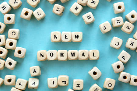 New normal word wooden alphabet cube. Blue background