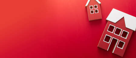 Wooden models of houses. Rent, buying or mortgage concept. Red background. Banner