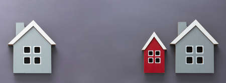 Wooden models of houses. Rent, buying or mortgage concept. Gray background. Copy space.