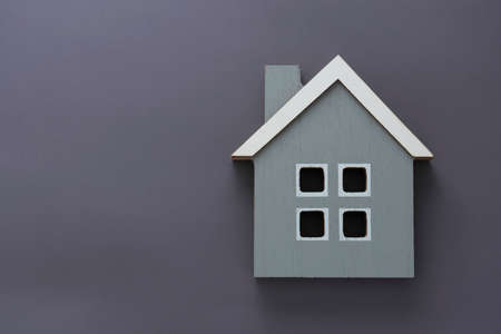House insurance and mortgage, buing or rent concept. Wooden model house over gray background, top view with copy space 免版税图像