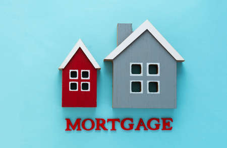Mortgage word and wooden houses. Home insurance. Rent, buy house. Blue background with copy space.