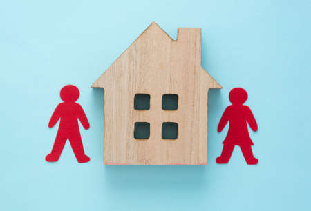 Buying a house, home insurance or mortgage concept. Couple silhouette with a wooden model house on blue background, flat lay. 免版税图像