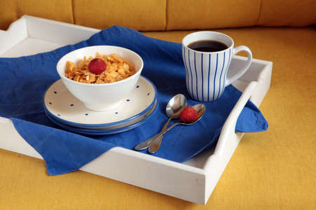 breakfast on a white wooden tablet and yellow couch. French crusty cornflaces, muesli, sweet berries and hot coffee for tasty morning meals. Delicious start of the day.