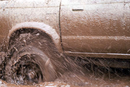 Off-road car going through deep mud holes. Detail of dirty car with filled mud - carwash concept. car wheels. dirty car wheel stands on forest