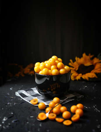 Yellow plums with lemon and lime on the black background. Ingredients for a jam. Food photography. Yellow sunflower, Autumn Foto de archivo - 137896546