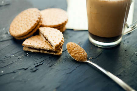 Cup of Coffee with a Cookie. Symbolic image. Coffee background. Sweet dessert. Wooden background. Close up.