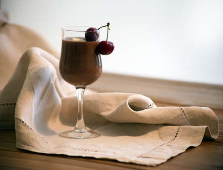Chocolate mousse in a glass with two cherries on the wooden table. Rustic style. Chocolate mousse with whipped cream in a glass on a rustic wooden table. Large glass of delicious chai latte and vanilla mousse, chocolate sauce