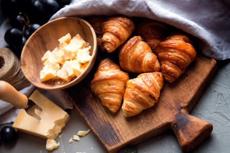 Original tasty French croissants with cheese and grapes on the wooden table. buttery flaky viennoiserie bread roll distinctive crescent shape. Cheese in bowl, knife, cutting board and napkins.