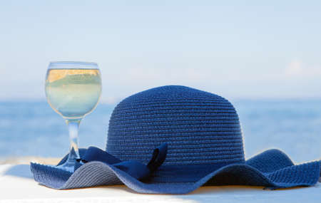 glass of white wine and a blue hat behind lagoon sea. Summer vacation concept.Beautiful summer day sea view. Luxury glass close-up. Romantic luxury travel moments and relaxation on tropical resorts