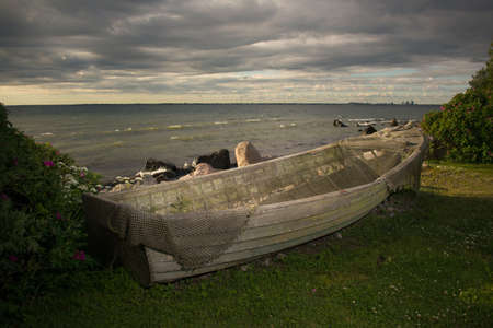 Old big fishing boat on a sea coast with fishing net. timber or wooden ship at the grass