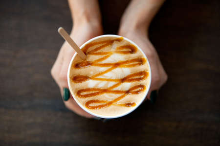 Caramel Big Coffee paper cup with milk in womans hand on the wooden table. cappuccino or latte drink, cup of coffee on table flat lay view. Cup of cafe au lait. Milk paintings. Hot Coffee for girl Stockfoto