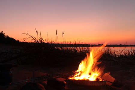Beach Campfire on Lake. Red sky Superior at sunset as vacation concept