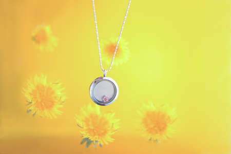 Silver necklace for her shining on yellow background with dandelions. Luxury silver jewelry chains with glass and crystals. Small Beautiful precious metal present for woman.