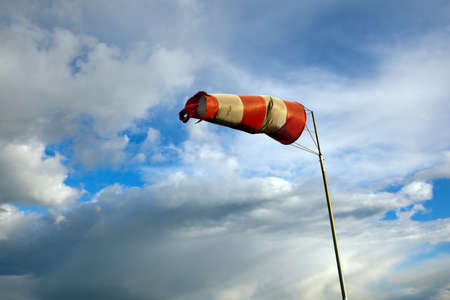 Red and white windsock blows against a blue sky